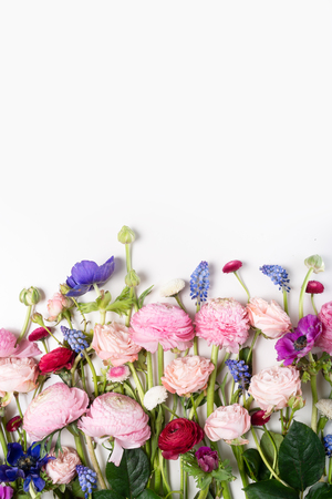 Flowers composition. Border made of roses, ranunculus, pansies and orchids flowers on white background. Flat lay, top view scene with copy space