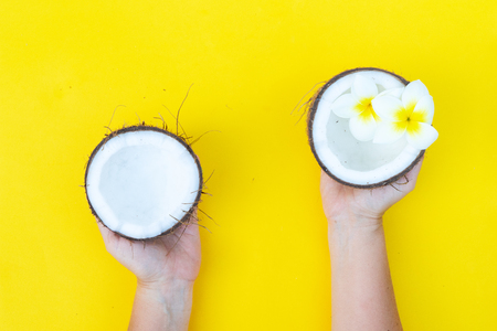 someone hands holding coconut cut open fruit on yellow background 版權商用圖片 - 122631683