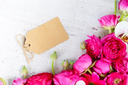 Flowers composition made of fresh ranunculus and orchid flowers on white aged wooden background. Flat lay, top view, copy space on paper tag