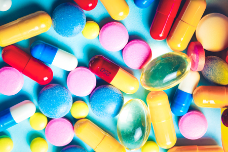 Pile of colorful medical pills on blue background, top view flat lay, toned