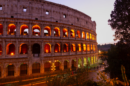 view of Colosseum illuminated at twilight in Rome, Italy