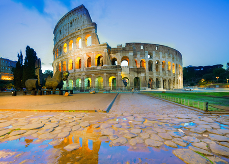 view of Colosseum with reflections puddle illuminated at night in Rome, Italy