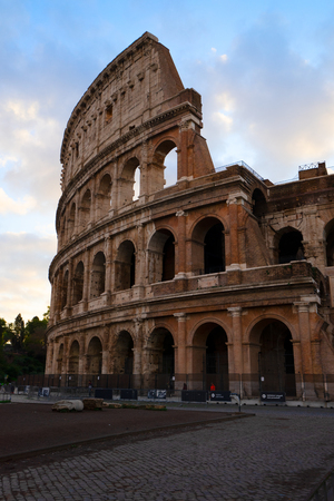 details of antique Colosseum with grass lawn in sunise lights, Rome Italy