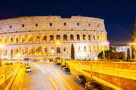 view of Colosseum illuminated at night with traffic lightst in Rome, Italy