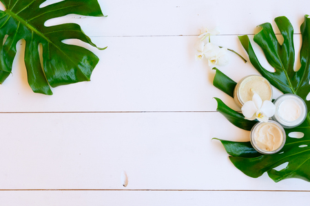 Coconut oil and cosmetics with green tropical green leaves on white wooden background
