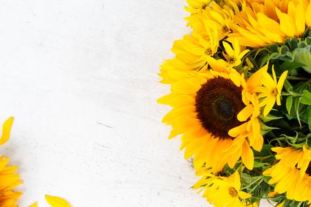 Zonnebloemen verse gele bloemen en bloemblaadjes op witte houten tafel achtergrond Stockfoto