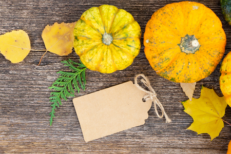 orange raw pumpkins with leaves on old wooden textured table, top view with copy space on paper tag