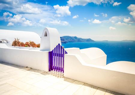 Blue gates against volcano caldera and sea, beautiful details of Santorini island, Greece, toned