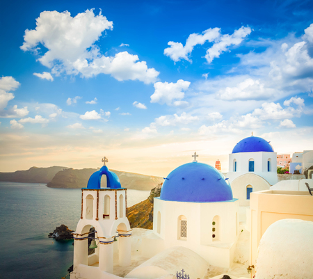 Traditional white Greek village Oia of Santorini, with blue domes of churches in sunset light, Greece, toned