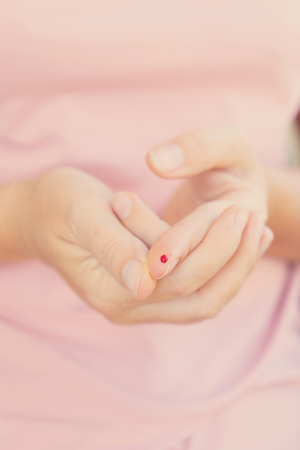 Someones hands with blood drop, measuring blood glucose level, toned
