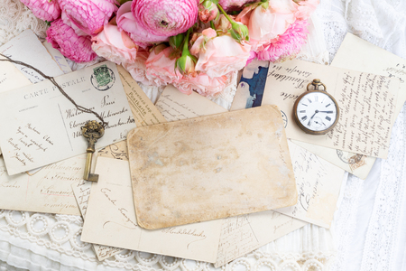 Pink and white roses and ranunculus with antique clock and skeletone key, copy space on vintage letter Stockfoto