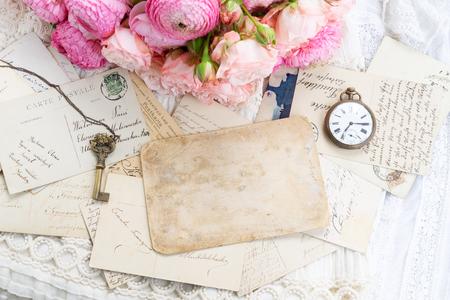 Rosa und weiße Rosen und Ranunkeln mit antiker Uhr und Skelettschlüssel, Kopienraum auf Vintage-Buchstaben