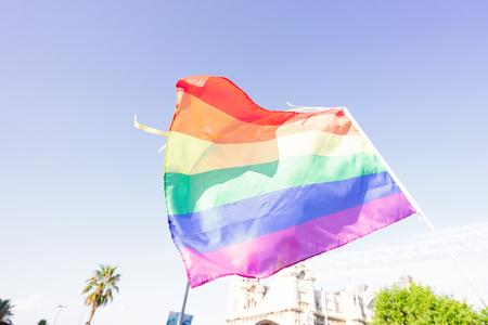 Rainbow flag background in blue sky of Barcelona, lgbt traditional symbol Stok Fotoğraf