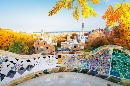 Gaudi mosaic bench detail and skyline of Barcelona from park Guell at sunset, Catalonia Spain at fall