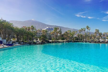 skyline of Puerto de la Cruz town with Teide volcano and pool, Tenerife, Spain