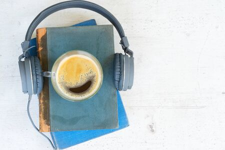Audio book concept. Headphones with books and cup of coffee on wooden table. Top view with copy space. Stockfoto