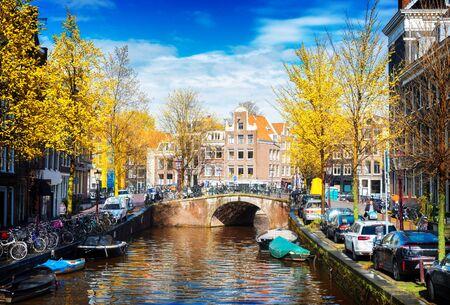 Gevels van Nederlandse historische huizen en brug over kanaal, het landschap van Amsterdam bij daling, Nederland