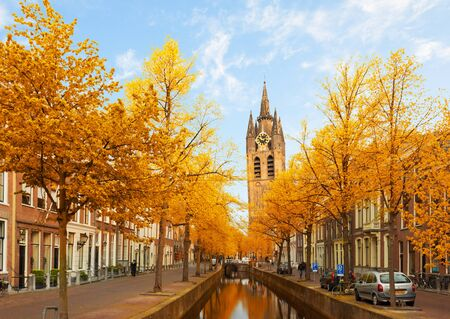 Street with canal and Old Church falling tower of Delft, Holland at fall Stock Photo