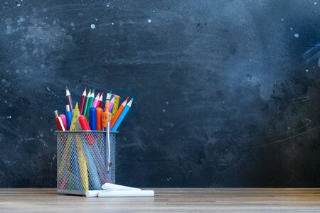 Back to school concept with colorful school supplies on blackboard