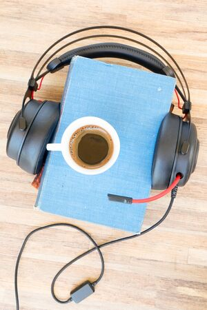 Audio book concept. Black headphones with books and cup of fresh coffee on wooden table. Top view