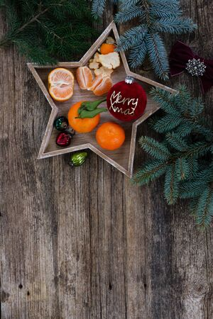 Christmas flat lay scene with tangerines and fir tree decotations, copy space on wooden background, Christmas celebration and gift giving concept