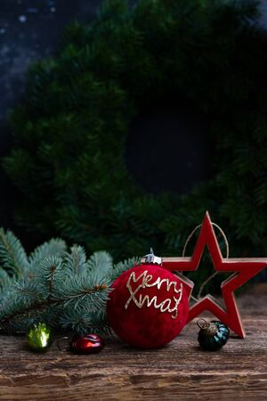 Christmas scene with red decorative ball and star, copy space on black wall background