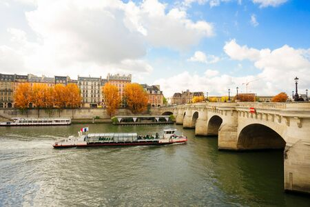 Pont Neuf and river Seine waters, blue autumn sky with clouds, Paris, France