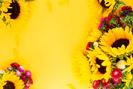 Sunflowers and aster fresh flowers frame , top view on yellow background with copy space, naturall fall flowers background Imagens