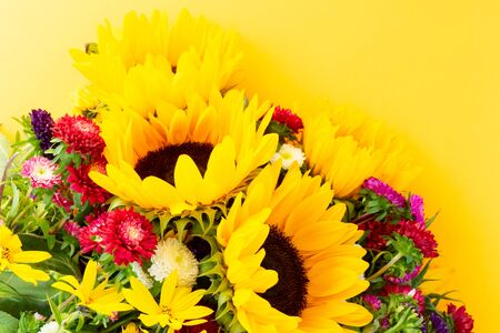 Sunflowers and aster fresh flowers, top view on yellow background, top view, naturall fall flowers background