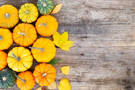 orange and green raw pumpkins on old wooden textured table, top view fla lay