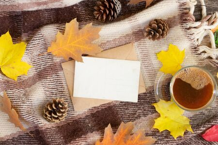 white empty card fall invitation, leaves and coffee on wooden autumn background with copy space on white paper note