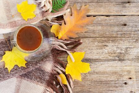 Fall leaves with cup of black coffee on woolen plaid autumn background with copy space