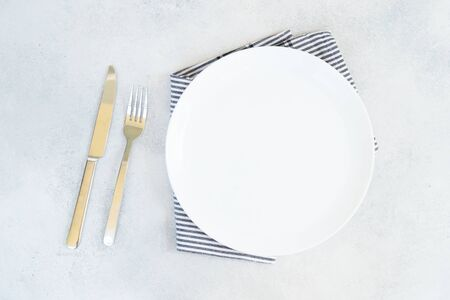 Abstract food background - empty white plate with blue napkin and cutlery