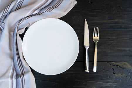 Abstract food background - empty white plate with napkin and cutlery over black table, top view
