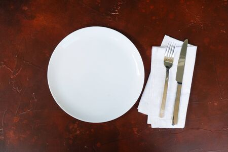 Abstract food background - empty white plate with napkin and cutlery over brown table, top view flat lay