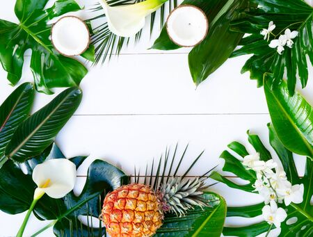 Summer flat lay scenery with tropical leaves and exotic flowers on white wooden background with copy space