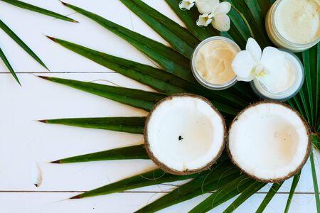 Kokosöl und Naturkosmetik mit grünen Palmblättern hautnah auf weißem Holzhintergrund