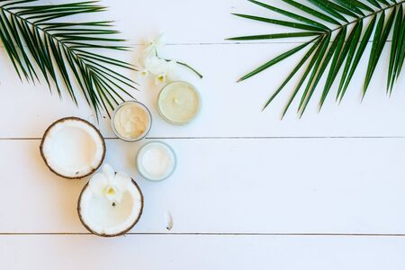 Coconut oil and cosmetics with palm leaves on white wooden background, top view