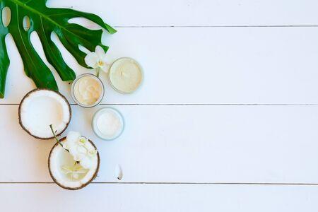 Kokosöl und Kosmetik mit Monstera-Blättern auf weißem Holzhintergrund, Ansicht von oben