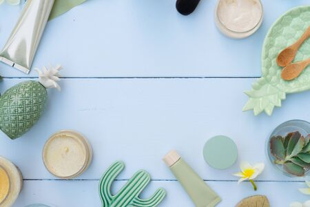 Beauty background with facial cosmetic products with succulents and make up brushes on blue wooden background top view flat lay frame with copy space, Beauty spa and wellness concept.