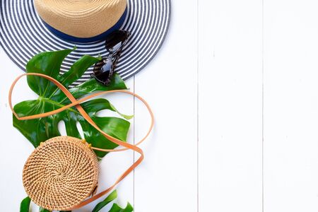 Summer flat lay scenery, bag, green leaves and cocnut on white background with copy space