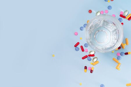 Coloful pills with glass of clear water over plain blue background with copy space. Medical pharmacy concept