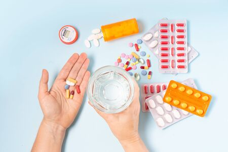 someone taking prescripted meds, hands with white pills and glass of water over blue background Reklamní fotografie