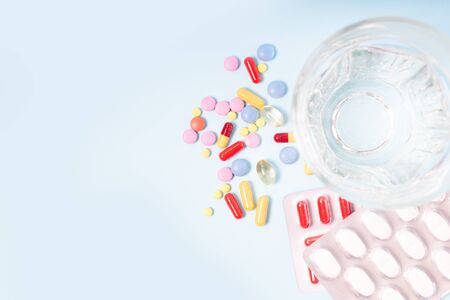 Coloful pills with glass of clear water close up over plain blue background with copy space. Medical pharmacy concept
