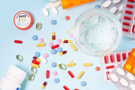Colorful pills with glass of clear water over blue background. Medical pharmacy concept, top view flat lay