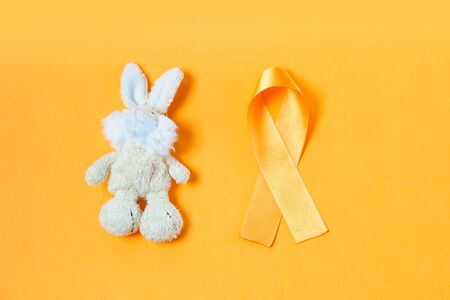 Childrens toy rabbit with a Childhood Cancer Awareness yellow ribbon on yellow background, top view