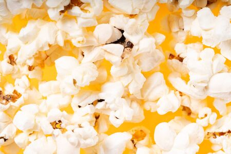 Scattered salted popcorn food textured close up background