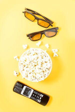 bowl of popcorn, nd remote control for TV and 3d glasses top view over yellow background, movie and cinema concept