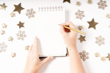 Wish list for Cristmas and New Year. Holiday decorations and ruled notebook with wish list and somwones hands, flat lay top view