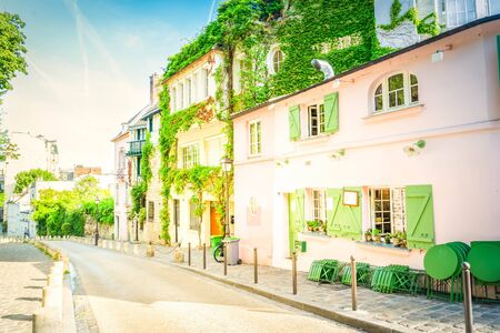 View of old street in quarter Montmartre in Paris, France. Cozy cityscape of Paris at summer. Architecture and landmarks of Paris, retro toned